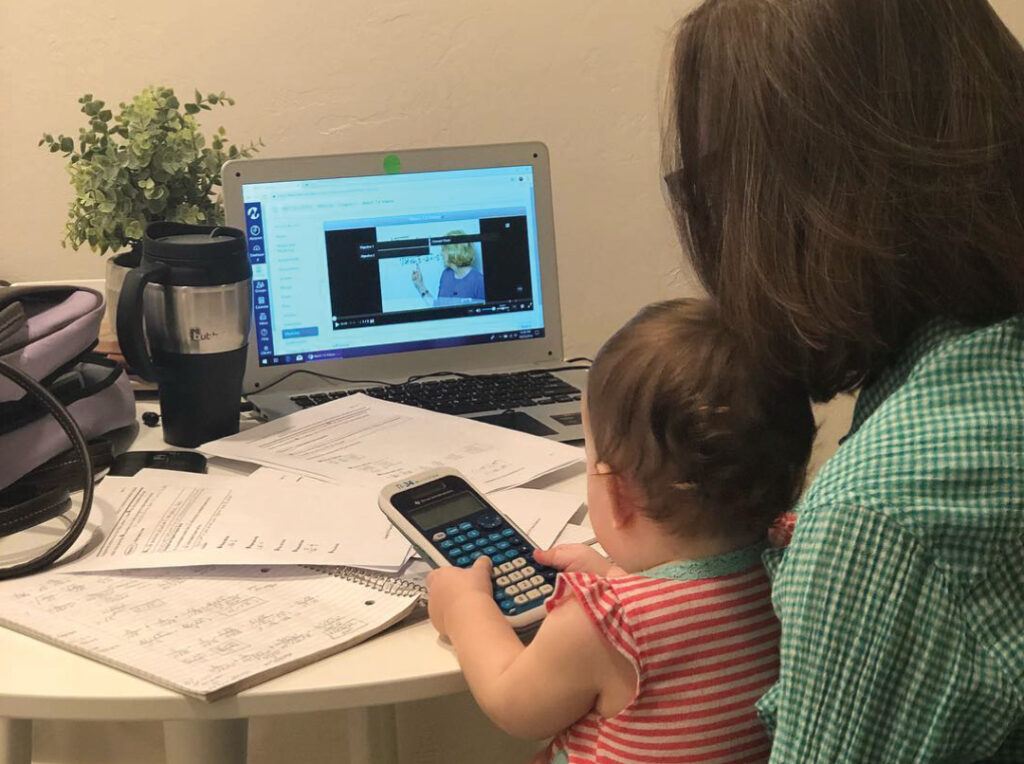 Image of woman holding baby on her lap while taking class at a a computer