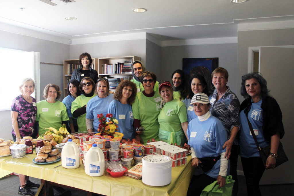 Image of a group of volunteers, smiling and standing around a table of food