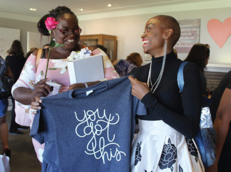Image of two women smiling at each other while holding up a Maggie's Place shirt