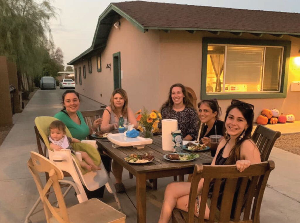 Image of women sitting at picnic table in the backyard of a Maggie's Place house